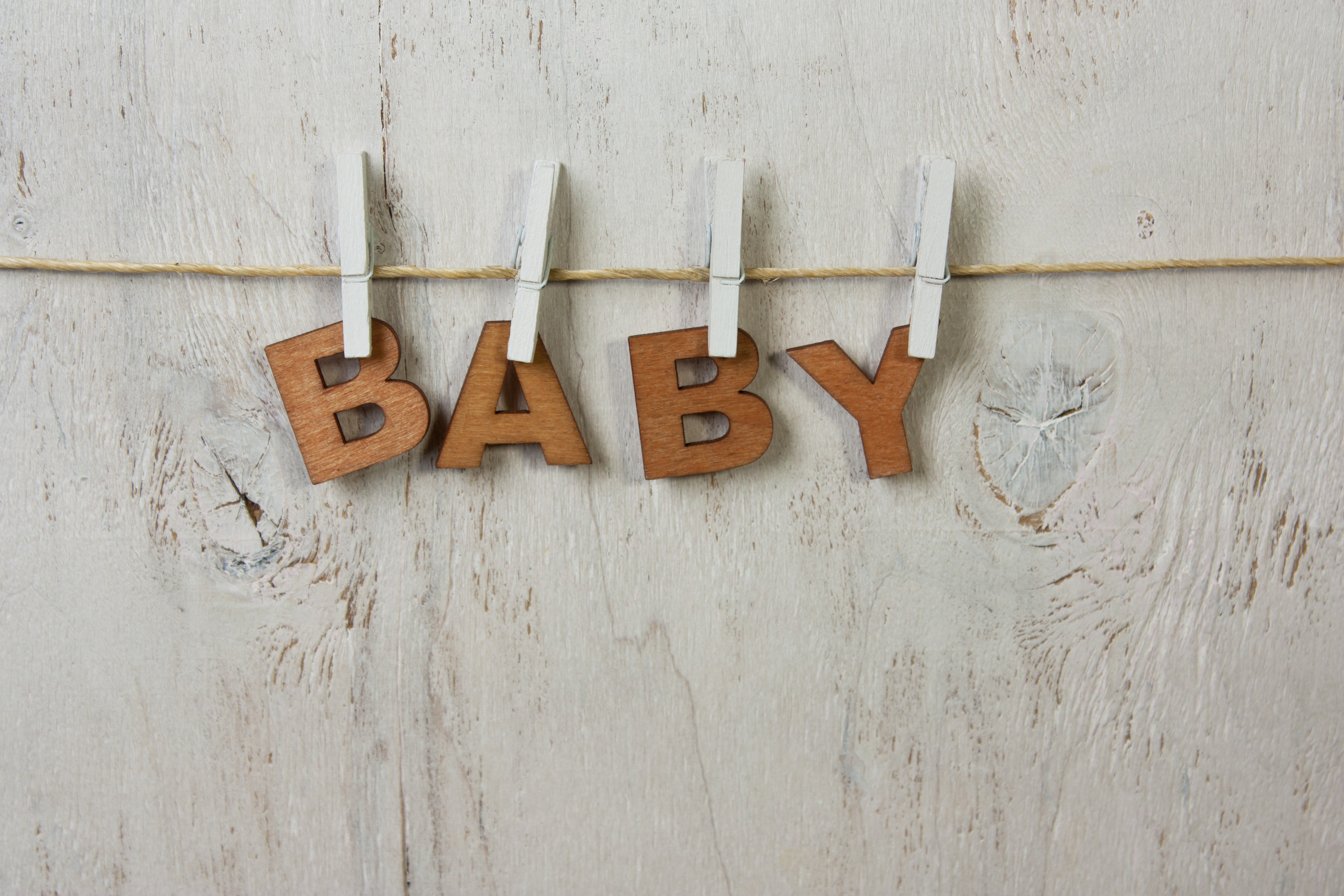 the word baby and clothespins on a white background old,rustic